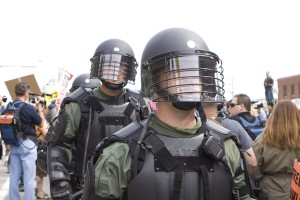 riot gear clad troops push through crowd at a peaceful permitted rally