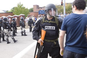 shotgun toting riot control police confronts college student