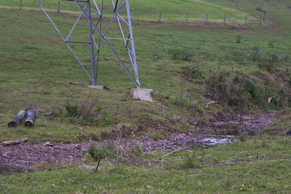 poorly managed land, grazing cattle in stream cause erosion that threatens power transmission tower