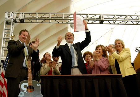 Environmentalist priae COrzine during signing ceremony for Global Warming Response Act. They later denounced Corzine - but not Jackson - for DEP's failure to implement the Act.